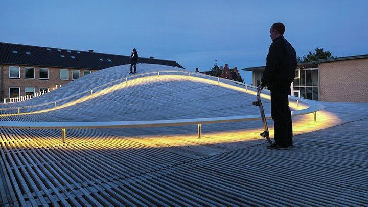 Linear LEDs on the underside of one of the benches traces the undulating curvature of the roof.