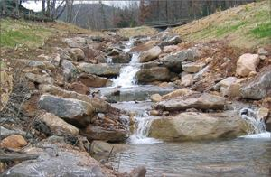 This view illustrates the recently reconstructed, extremely steep (11%) stream channel. Construction, using the keystone approach, created a nonuniform stream appearance. The channel will be thoroughly naturalized only after the planted streambank vegetation has become established.