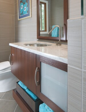 The rich tones of this custom mahogany vanity add a touch of drama to the guest bathís otherwise neutral palette. Both the large glass-door storage cabinet and the 6-inch high shelf are mounted on the wall. The cabinet is topped with a Carrera marble countertop set with an undermount stainless steel sink.