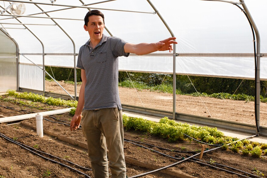Matt Kelterborn, Eden Hall Farm assistant, discusses benefits of the campus' movable hoop house. A variety of vegetables are grown year-round, many of which are served in the university's dining hall.