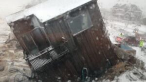 A house slides into the ocean waters at Plum Island, MA, after being hit by pounding waves from Winter Storm Saturn on Friday, March 8, 2013.