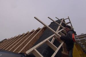 Todd lifts an overhang outrigger into position on the steep gable roof of the addition.