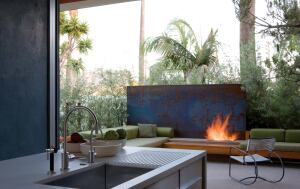 A sliding glass wall system allows the kitchen to become an indoor/outdoor room. A plate of cold-rolled steel serves as a backdrop for the patio's gas fireplace. Interior elements deploy materials—Corian, stainless steel, and teak—in broad, simple forms.