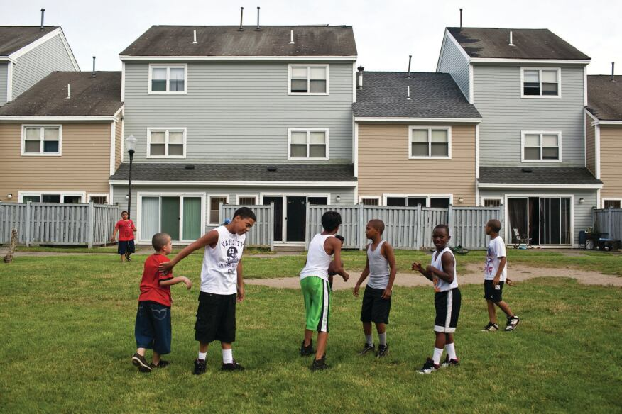 Neighborhood children play football behind townhouses in Harbor Point.