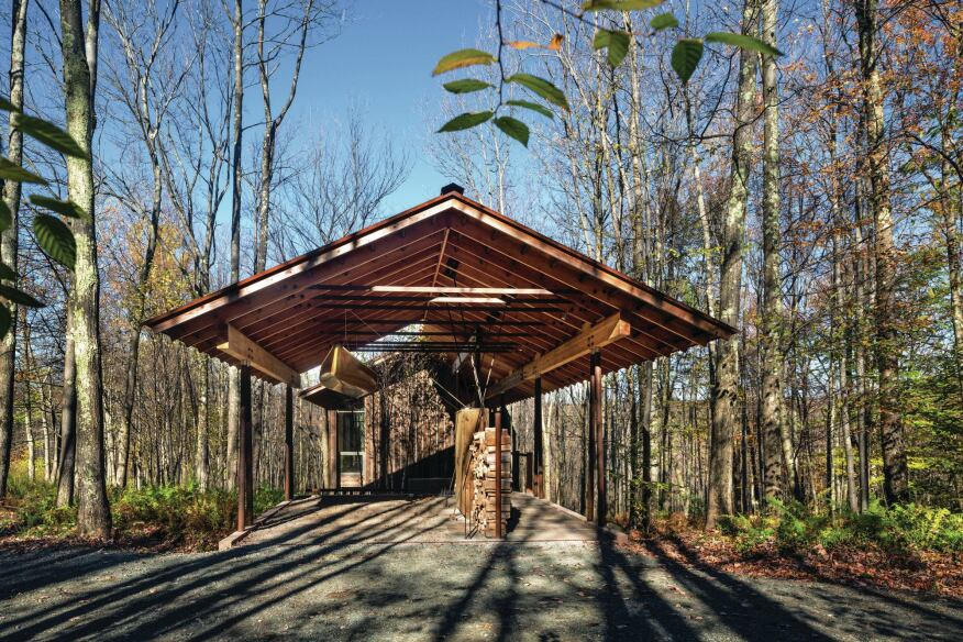 The entrance to the guest house and artist studio is sheltered by a pitched-roof canopy. Steel storage racks for firewood and bicycles separate the entry walkway from the adjacent parking space.