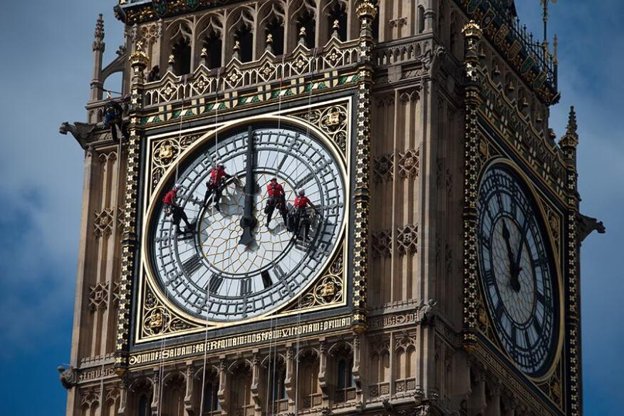Workers clean the face of the Big Ben clock in London.