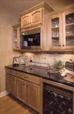 The nearby butler's pantry (right) has cabinets for additional storage and serving space. The homeowner chose a built-in Miele coffee machine and an undercounter wine chiller for entertaining.