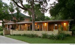 Cedar shingles, a series of French doors, and an added-on carport rescue this 1960s ranch house from aesthetic oblivion.
