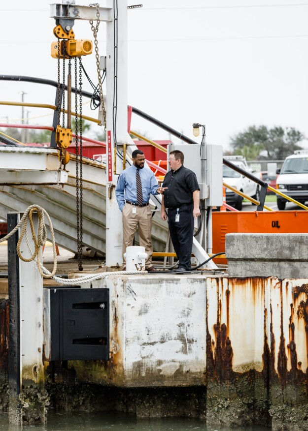 Lockwood, Andrews & Newnam consulting engineer Percy R. James, PE, LEED AP BD+C (left) confers with Texas DOT Marine Engineer Donald Marquise at a work dock that's being reconfigured to fit more ferries and enable agency maintenance technicians to service the vessels from any berth.