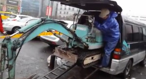 mini excavator being loaded into a minivan