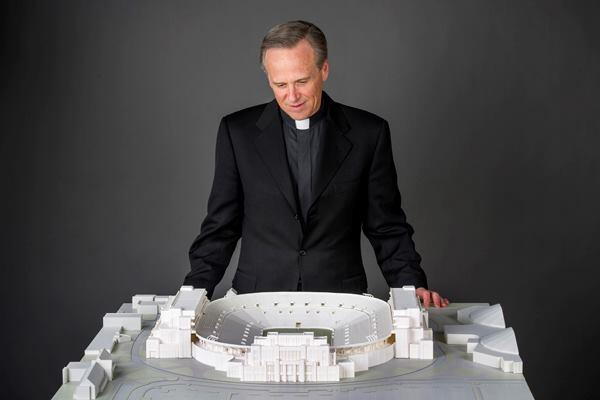 Rev. John I. Jenkins, the university's president, looks at a model of the project.