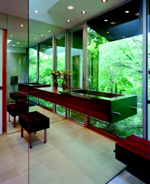 """To create a master bath with windows that frame the wooded view, architect Kevin Alter designed a floor-to-ceiling glass wall and a glass-enclosed shower.  He felt that a standard vanity would look too heavy for the space, so he opted for a """"floating"""" cherry-wood piece with a custom stainless steel trough sink.  The team created the look by bracing the unit between the tempered glass shower wall and a mirrored wall. Alter says the hardware mounts are similar to those used for glass cases in jewelry stores.  Contractor Joseph Zambarano says the drawers in the vanity are 4 inches short of the back wall, providing space for water supply lines and a trap used for disabled installations.  These pipes run along the rear channel and connect to the main pipes behind the mirrored wall.  In addition to the vanity, there is a cantilevered ipe wood bench, which is attached to the glass panel using the same hardware mounts.  A stainless steel leg supports it on the other side."""