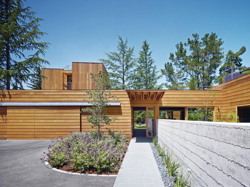 The landscaped entrance to the wood-clad Low/Rise House is at the end of a Vermont slate walkway, and flanked by a board-formed concrete wall that separates parking from private garden; the wall's formwork was re-used as floor joists.