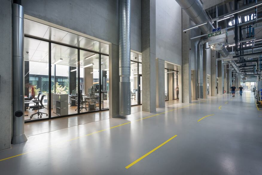 Glass-enclosed offices overlook both the courtyard and the factory floor