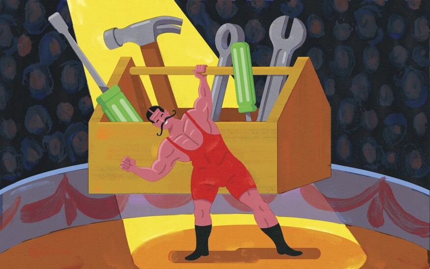 Strongman holding up a box of tools