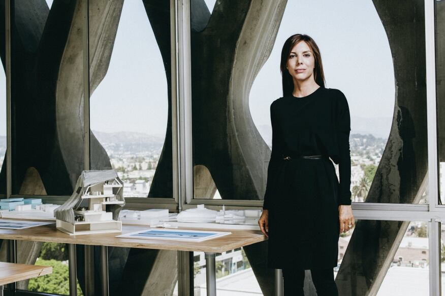 Jennifer Marmon stands beside a section model for PAR's Helsinki Central Library proposal. The firm collaborated with Arup on a highly technical, transparent façade with thermal properties.