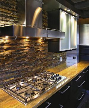The base wood cabinets have a black finish and are topped with orange travertine that ties in with the orange walls and brings out the rust shades in the stone backsplash. The backsplash is stone veneer manufactured in 3-by-12-inch sheets that are installed like tile. The same stone veneer was also used to cover the original white stucco area around the fireplace.