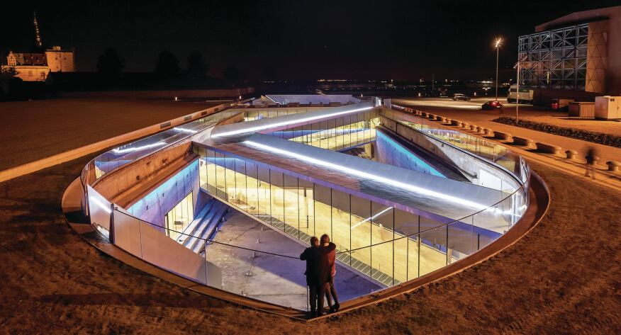 The Danish National Maritime Museum glows from within at night.
