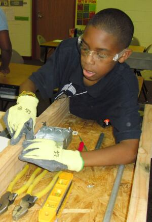 The young participants learn the basics of electrical wiring, plumbing, carpentry, and more from builders and contractors who visit each week.