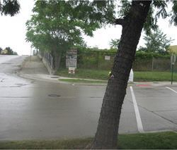 In Detroit, a curb ramp is located too far from the corner, and a nearby tree on the west side of the intersection can obstruct drivers who don't expect to encounter a pedestrian crossing. Photo: H.R. Gray