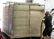 After applying a release agent and a waterproofing layer to a male mold, a worker encapsulates the liner and steel reinforcing frame in polyurethane spray foam. Completed tanks range in size from 5 by 5 by 4 feet to 8 by 8 by 20 feet.