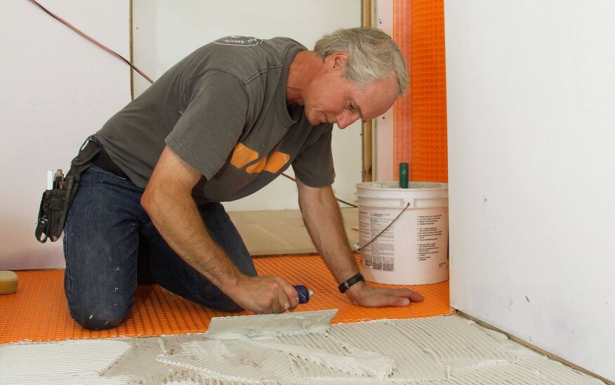 Tile contractor Tom Boucher of Integrity Tile, based in Kennebunk, Maine,  applies latex-modified Bostik Ditra-Set mortar to an Advantech subfloor to make a mortar bed for adhering Schluter Ditra decoupling underlayment membrane for a custom marble tile floor in a bathroom for a new house under construction next to the ocean south of Portland, Maine.