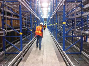 A crew inspects the floor after a completed grind at a very narrow aisle facility.