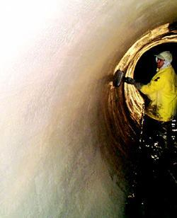 Workers repairing a sewer pipeline for the Middlesex County Utilities Authority in New Jersey hand-applied Sauereisen's Underlayment No. F-120, which enabled repair of the pipe from the inside.