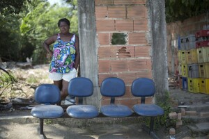 "Sandra Regina poses for a photo at her home at the Vila Autodromo slum, in Rio de Janeiro, Brazil, Wednesday, March 9, 2016. Vila Autodromo has now been largely destroyed to make way for an access route into the Olympic Park. Sandra Regina who has lived in the community for 21 years, questioned the suggestion that residents would need to vacate the area while the construction went ahead. ""He'll never let us come back if we leave,"" referring to the city's Mayor Eduardo Paes. ""Believing in Eduardo Paes is like believing in Father Christmas or the Easter Bunny,"" she said. (AP Photo/Silvia Izquierdo)"