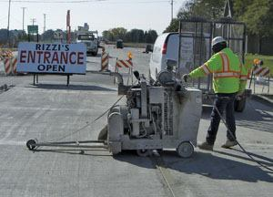 A worker sawcuts transverse joints into pavement on the State Route 59 project near Joliet, Ill.