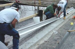 Mounting rails are lowered into position into an epoxy leveling bed.