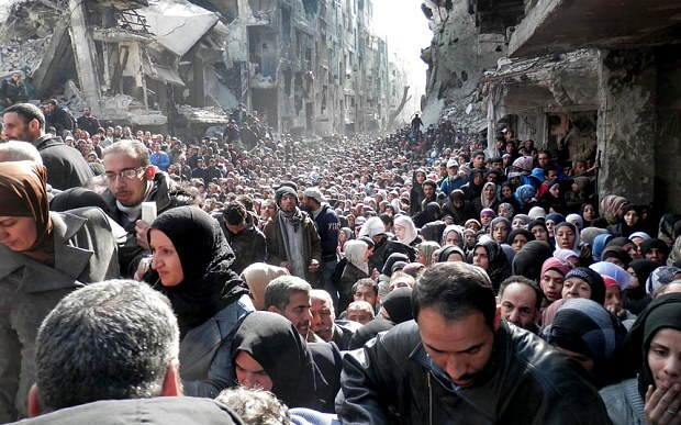 Palestinian refugees queue for food and supplies in Damascus, Syria, in January 2014