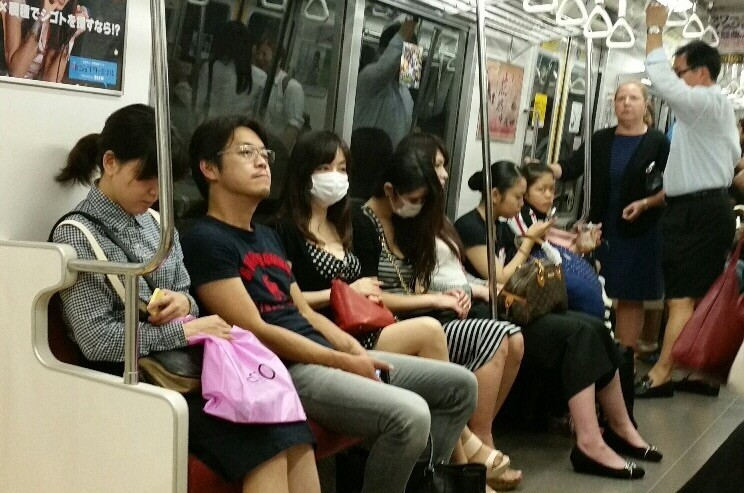 Commuters wear masks on a subway ride in Tokyo