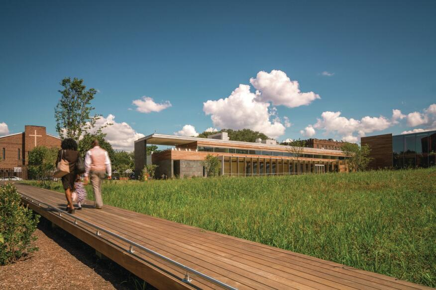 A wooden bridge connects the historic Weeksville homes to the new structure.