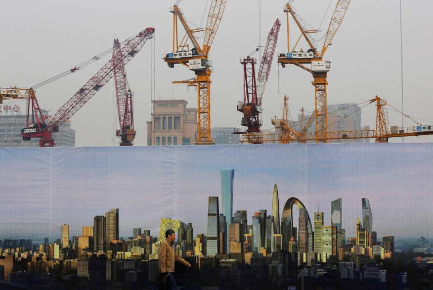 A man walks past a billboard display showing the scenic of Central Business District near a construction site in Beijing. China's growth could decline to close to 7 percent next year but Beijing should focus on overhauling its economy instead of trying to stick to official growth targets, the World Bank said Wednesday.