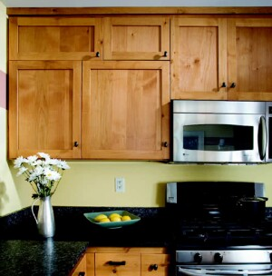Asymmetrical alder-wood cabinets and three types of remnant granite give this traditional-looking kitchen an unorthodox twist.