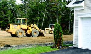 SETTING THE GRADE: Excavators grade a lot next to a completed home at Hovnanian's Four Seasons  neighborhood in Smithville, N.J. The company's evenflow system aims to start  and complete a consistent number of units each month, for smooth, streamlined  production.