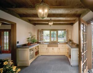 Rough-hewn timber beams and a bluestone floor impart an authentic feeling to this country French-style potting room.