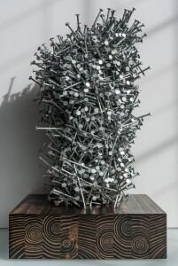 """""""Unfastened"""" aggregates approximately 3,900 nails on a 2-foot-by-4-foot stained wood base."""