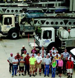 Mitch Kueckelhan, center in gray shirt and sunglasses, and his team, surrounded by the equipment that keeps the operation moving.