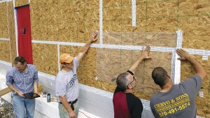 Architect Richard Pedranti, HERS rater Pete Vargo, consultant Bryan Kehm, and builder Rob Ciervo tape plastic over the OSB sheathing during a blower-door test.
