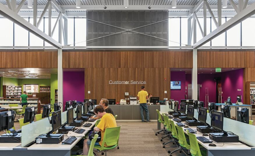 Allsteel benching with computer terminals exemplify the library's evolving role in the information age. The lime green children's area, at left, features letterforms suspended flat from the ceiling.