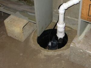 The same drain pipe used in the sculpture forms a pit for a sump pump.