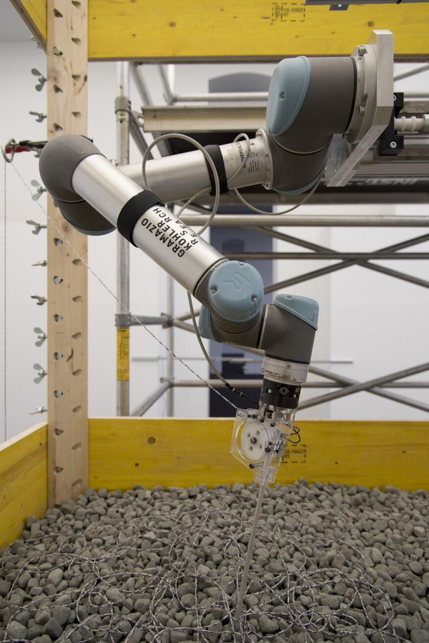 A robotic arm positions the granular, rock-like material around layers of textile filament.