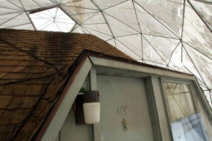 A fabric dome covers the original structure, itself covered in many layers of asphalt roofing shingles.