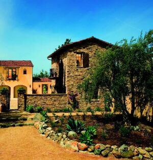 ARTFUL COMPOSITION: An antidote to big-box floor plans, Plan One, which garnered home of the year honors, is a medley of asymmetrical structures. With its clay tile roofing, iron balconies, and curved arcades, the 4,014-square-foot home evokes the region's early Spanish influences.