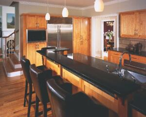 The Kitchen is part of a remodel that included a breakfast room, living room, and office.  Brown granite countertops and a raised bar made of Silestone provide a contrast to the natural maple cabinets.