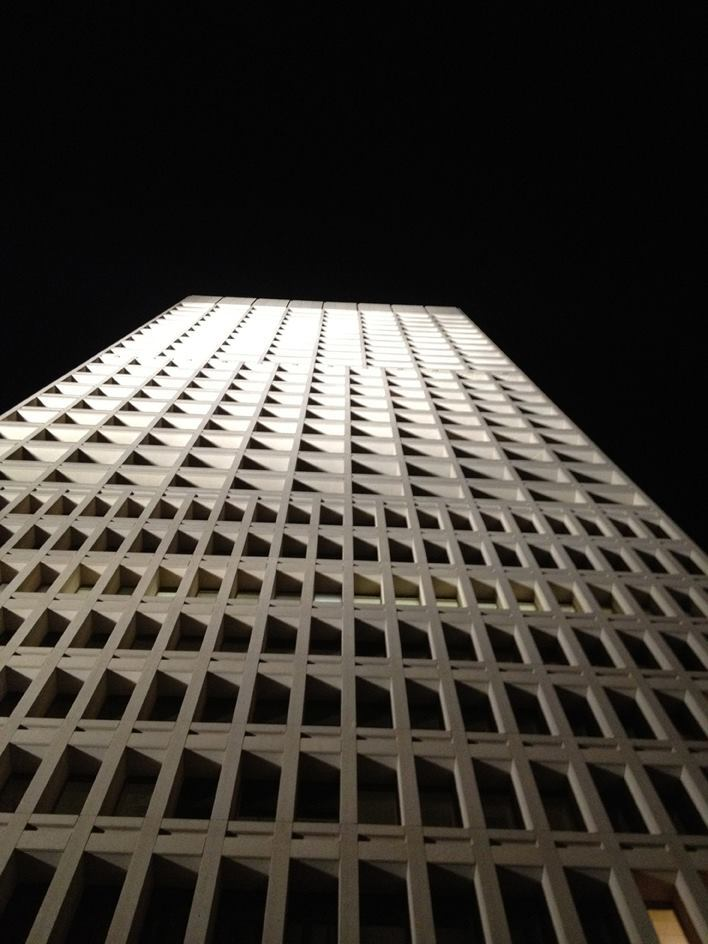 The floodlight aiming angles create a bold play of light and shadow on the tower façades.