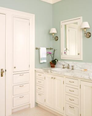While Wilson created a separation of spaces in this master bath, he ties it all back together with a band of marble that begins as the sink counter and circles the room at counter height.