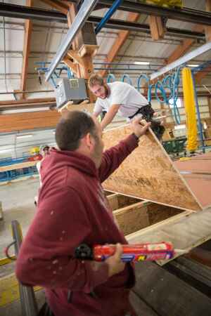 Unity Home employees Brett Ramsay (foreground) and Chris Smith work on the assembly of flooring at the company's Walpole, N.H., factory.